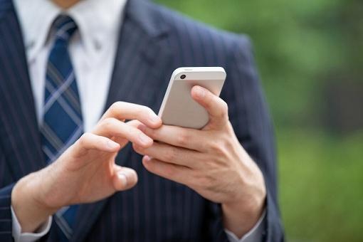 携帯を使う男性の画像