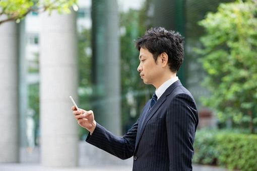 携帯を触る男性の画像