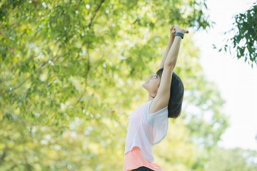 背伸びする女性の画像